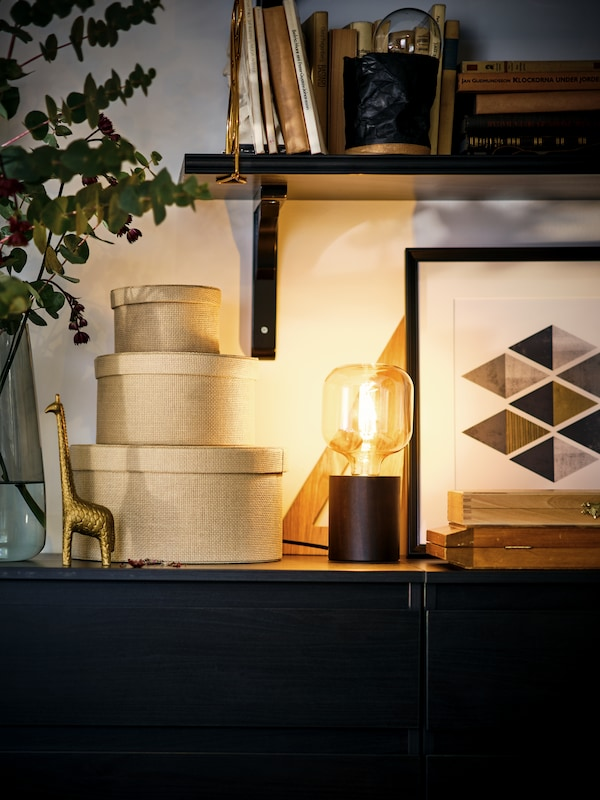A MARKFROST table lamp lights up a stack of beige KVARNVIK boxes and decorations atop a black-brown KULLEN chest of drawers.