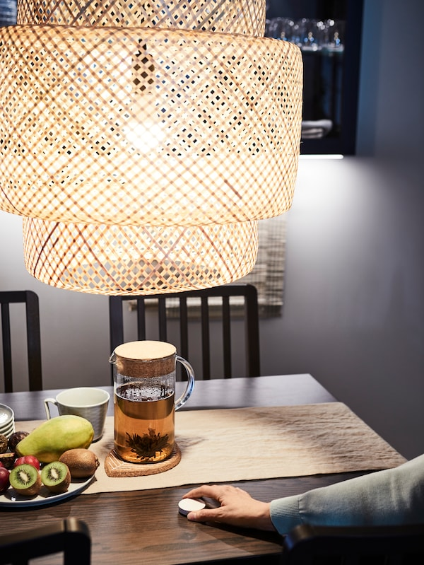 A hand with an IKEA Smart home device on a table, with a jug, cup, a plate of fruit, chair, under a large lampshade.