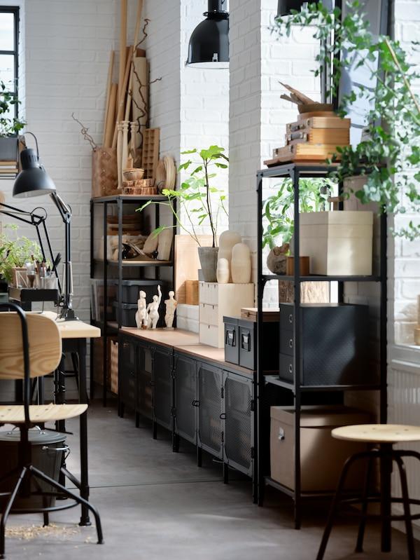 وحدات رفوف سوداء مع صناديق وأغراض خشبية وطاولة تلفازسوداء مع صناديق في الأعلى ونباتات في أواني.