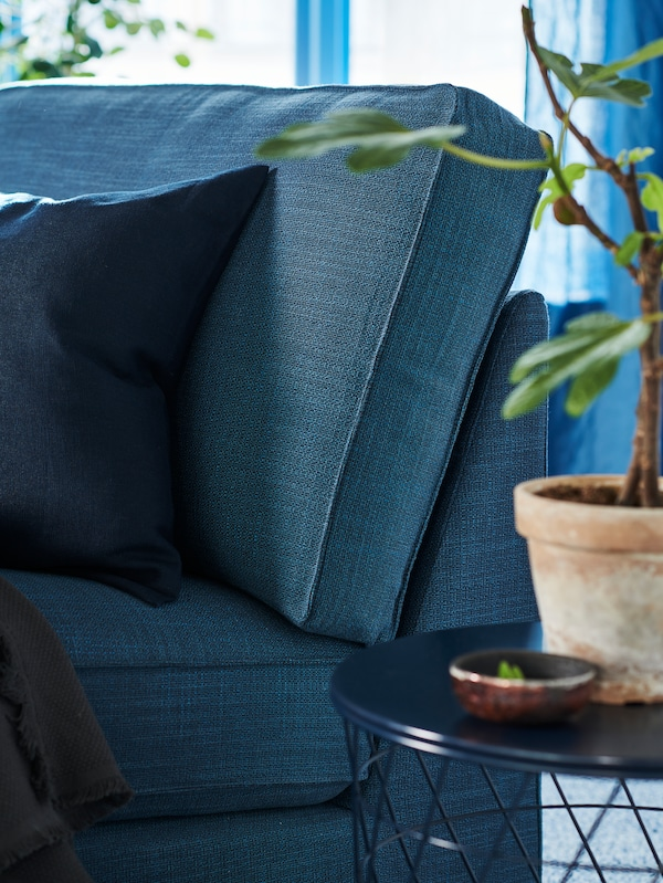 Colțul unui șezlong KIVIK albastru lângă o măsuță de cafea albastră cu o plantă.