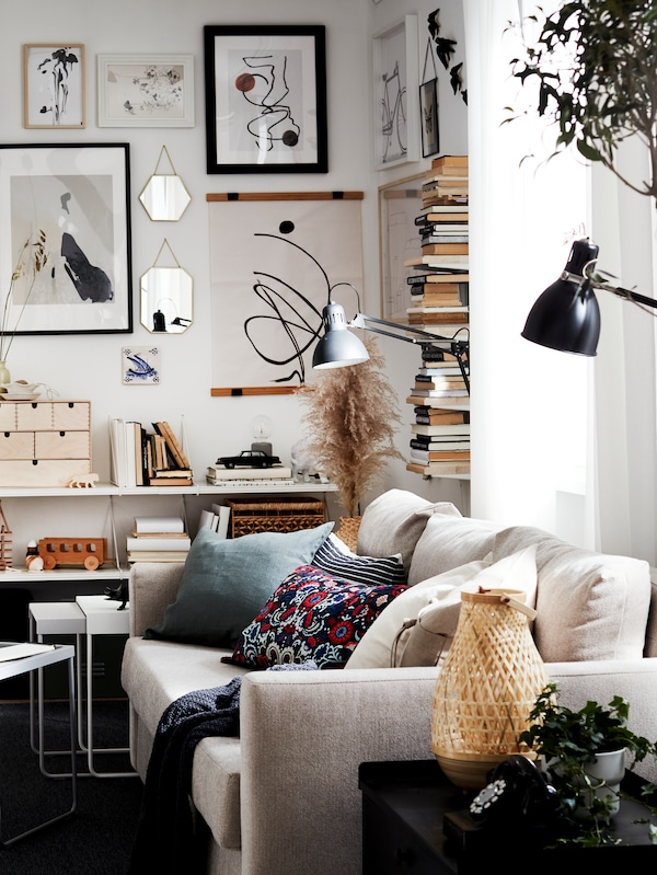 A room with a sofa holding diverse cushions, books in bookcases, shelves and pictures in picture frames on the wall.