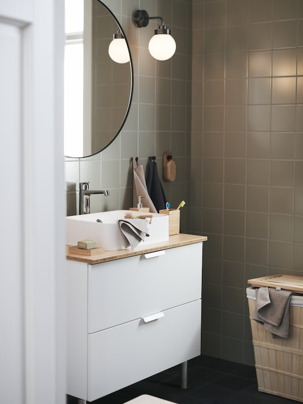 A white sink bathroom cabinet with a wood top, a white sink, and a round mirror hanging above.
