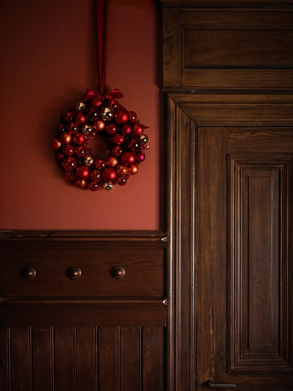 Julekrans hengende på veggen ved en dør.