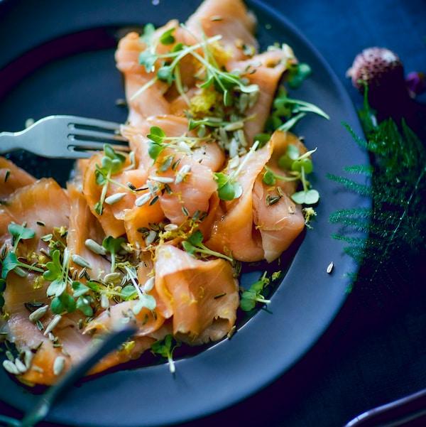 Niebieski talerz z wędzonym na zimno łososiem SJÖRAPPORT przybranym pestkami słonecznika i świeżymi ziołami.