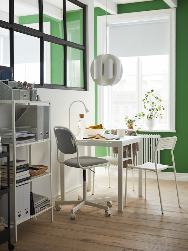 Hvidt bord og to stole, hvid/VISSLE lysegrå skrivebordsstol, en hvid LED-skrivebordslampe og en reol.