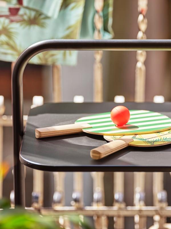 Dos palas estampadas en verde y amarillo, y una pelota sobre una mesa negra, en un balcón.