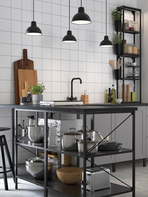 Cucina angolare ENHET con frontali grigi e scaffali antracite con erbe aromatiche in vaso e utensili sui ripiani.