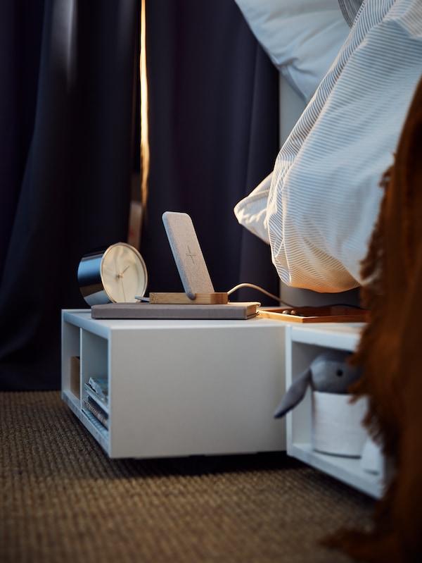 ที่เก็บของใต้เตียง/โต๊ะข้างเตียง FREDVANG/ฟรียดวัง ที่มีนาฬิกาปลุกและของอื่นๆ วางอยู่ ตั้งอยู่บนพื้นโดยบางส่วนอยู่ใต้เตียง