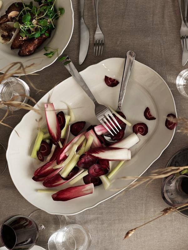 Un plat de service blanc contenant des crudités très colorées, et une fourchette et une cuillère sur une table couverte d'une nappe beige.