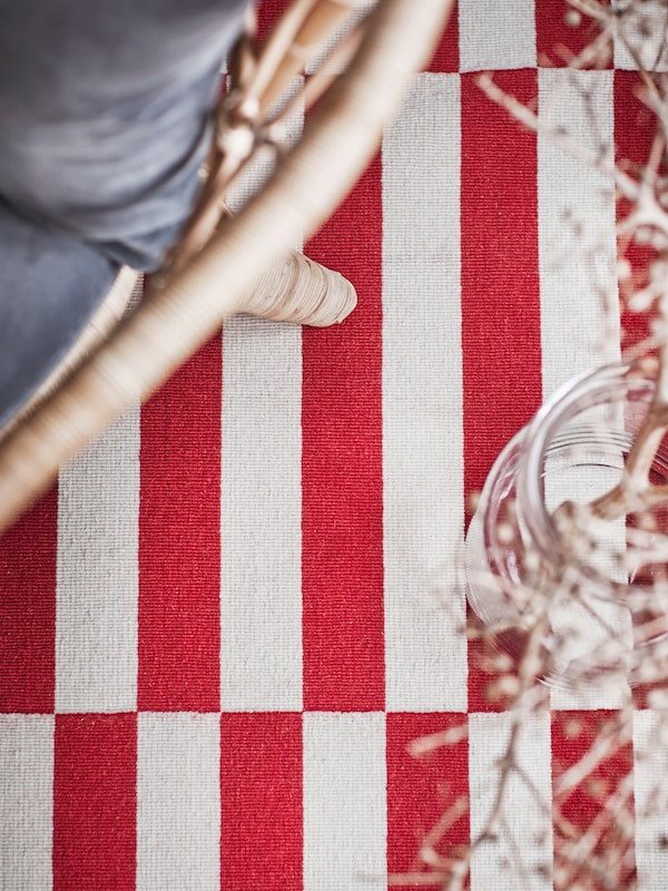 A rug with thick red and white stripes, and the corner of a bamboo chair with a cushion on it.