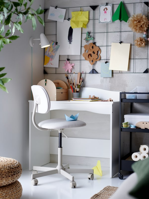 A white SMÅGÖRA children's desk with a swivel chair, a black trolley, a memo board with clips and drawings, and a wall lamp.