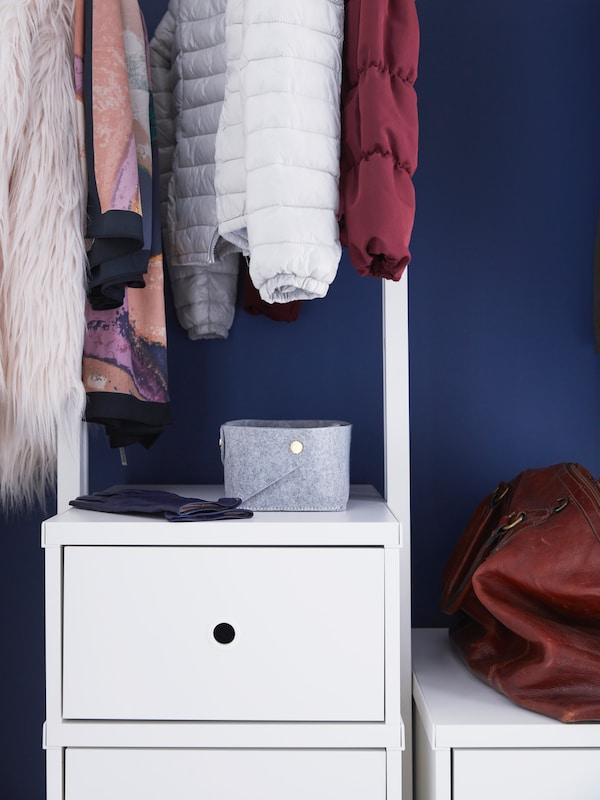 Un moble de caixóns ELVARLI cunha caixa de almacenaxe pequena de cor gris enriba, con roupa colgada enriba contra unha parede azul.