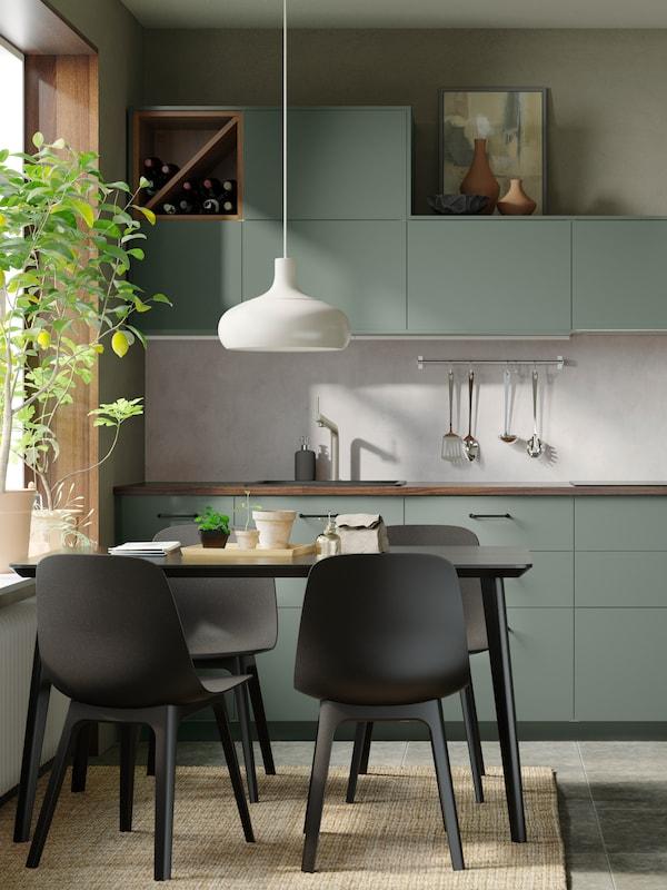 Eine Küche mit BODARP Fronten in Graugrün. Davor sind ein Tisch und vier ODGER Stühle neben einem Zitronenbäumchen auf einer Fensterbank zu sehen.