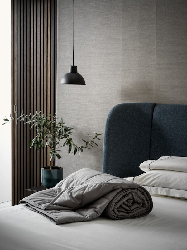 A dark grey ODONVIDE weighted blanket on a blue TUFJORD upholstered bed with a pendant lamp beside it, in a grey bedroom.