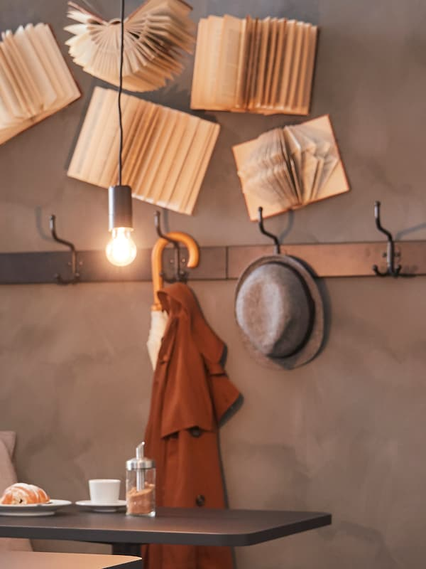 Zo stropu je zavesený čierny kábel so žiarovkou a na stene vešiaková lišta s háčikmi, na nej klobúk a dáždnik.