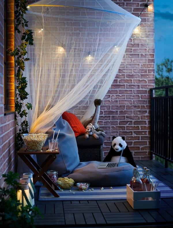 Balkon přeměněný na pohodlné soukromé kino pro rodinnou filmovou noc, s polštáři, občerstvením a plyšovými hračkami.