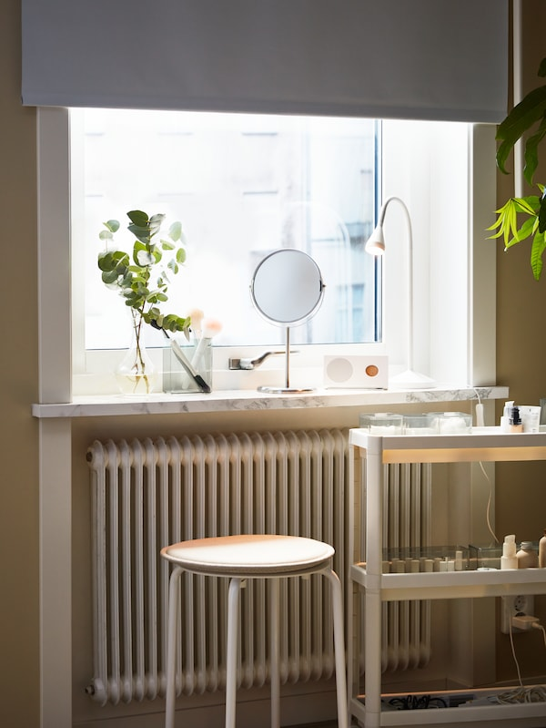 A mirror placed on a window sill with a TRENSUM mirror and a white table lamp on the window sill, plus a white trolley.