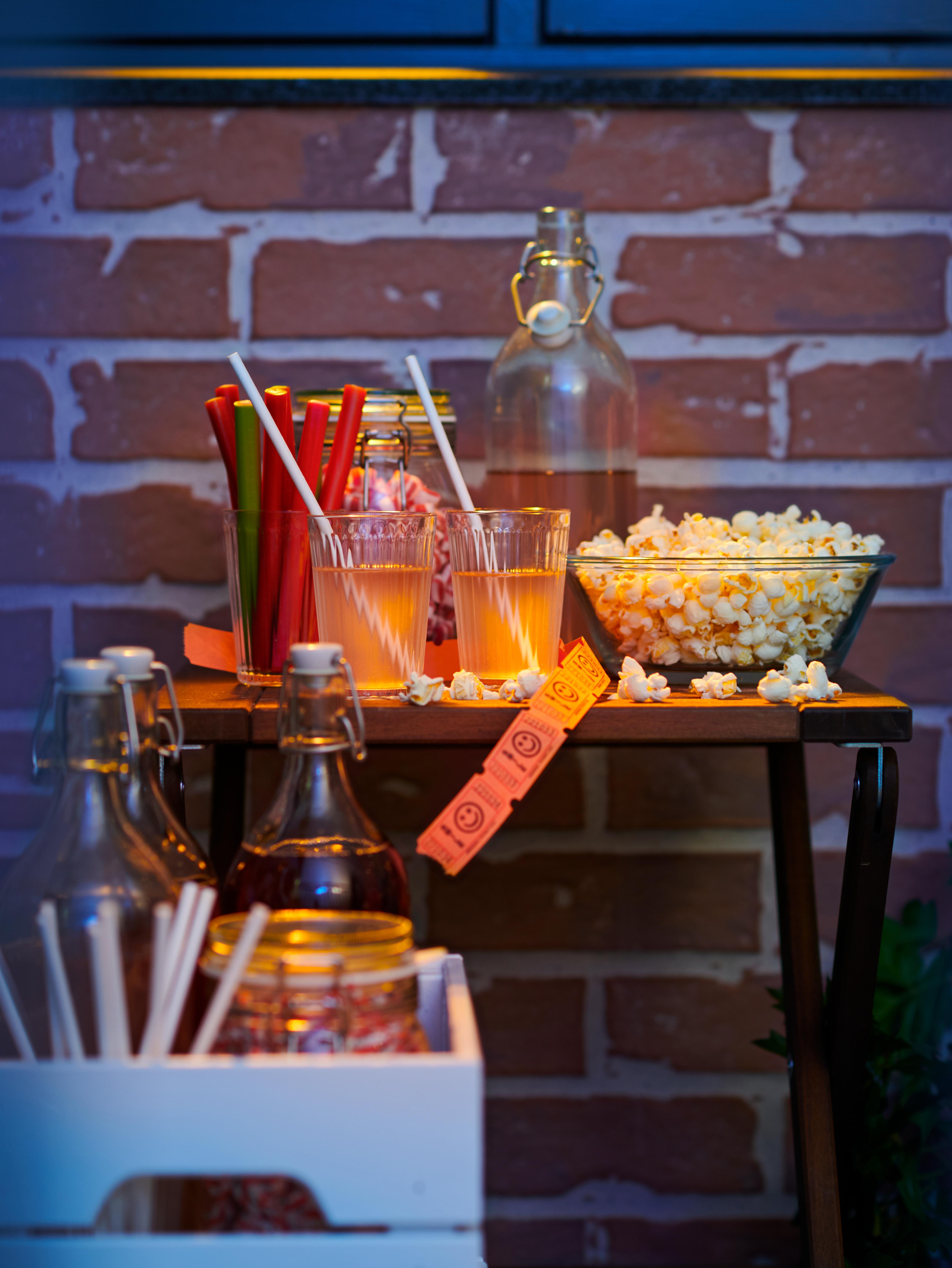 Ett bord med snacks på en tegelbalkong som förberetts för filmkväll. På bordet finns en skål med popcorn och drycker med FÖRNYANDE sugrör av papper.