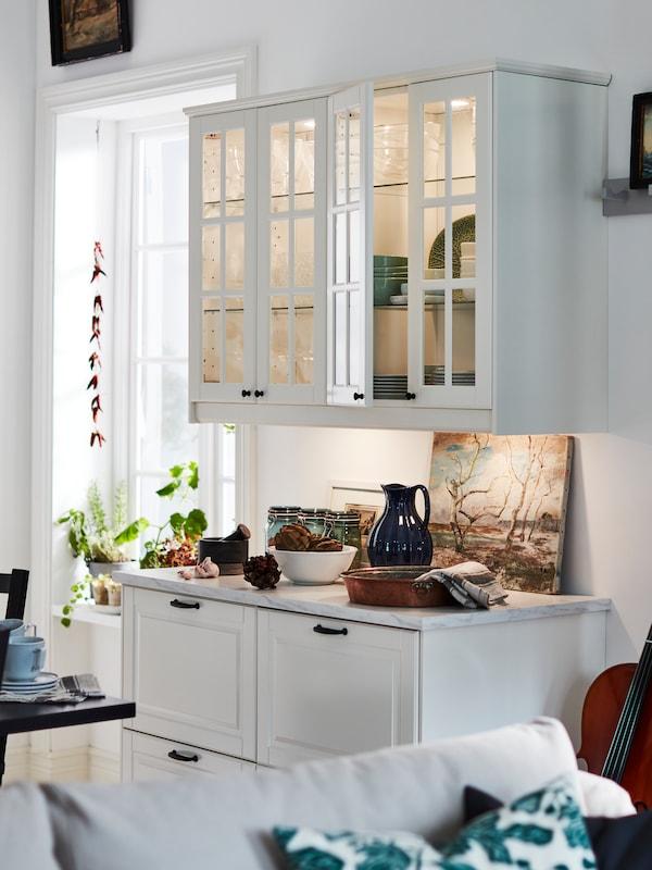 Dvě elegantní bílé spodní skříňky se zásuvkami pod dvěma tradičními nástěnnými skříňkami se skleněnými dvířky a osvětlením.