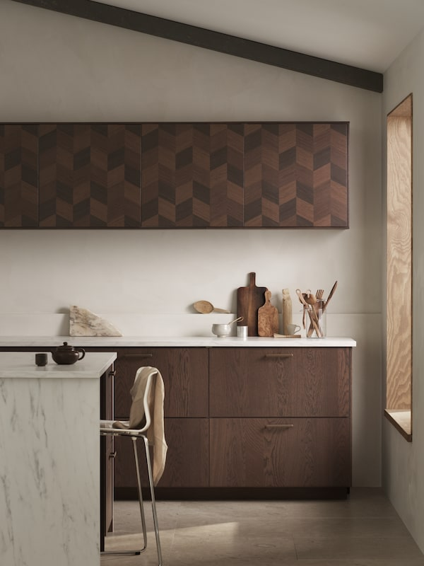 A kitchen with an island in marble effect a GLENN bar stool, brown SINARP drawers and brown patterned HASSLARP doors.