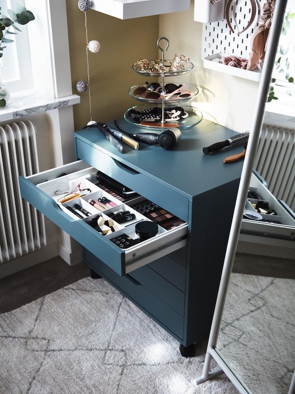 Ein ALEX Schubladenelement mit einer geöffneten Schublade. Darin sind Frisierutensilien zu sehen und darüber ein weisser Standspiegel.