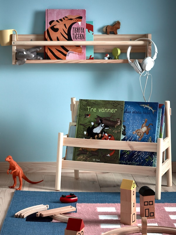 A FLISAT wall storage and book display holding books and toys in a blue child's room with an UPPTÅG rug with toys on it.