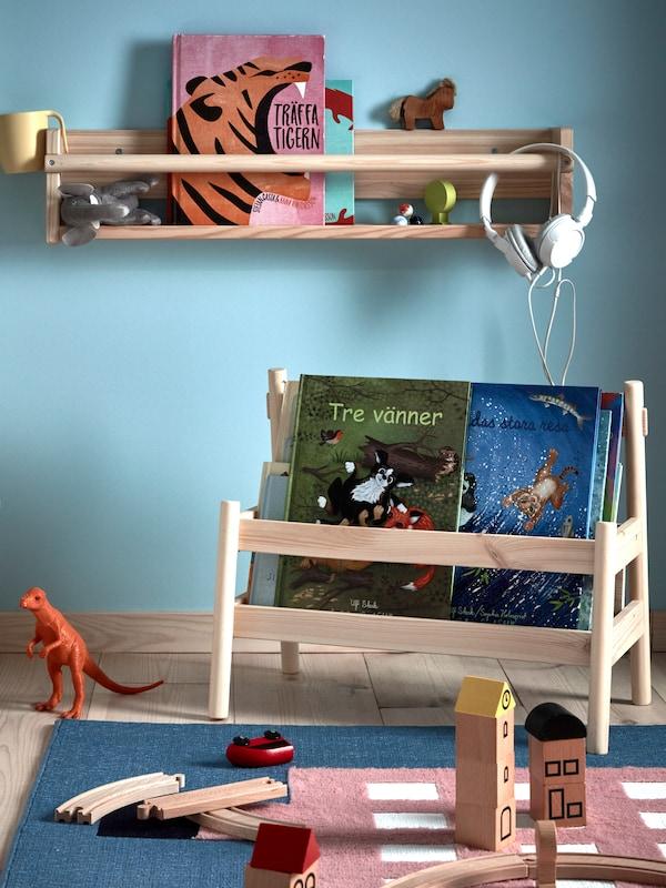 Sistema de almacenaxe en parede e expositor FLISAT con libros e xoguetes nun cuarto infantil azul cunha alfombra UPPTÅG con xoguetes.