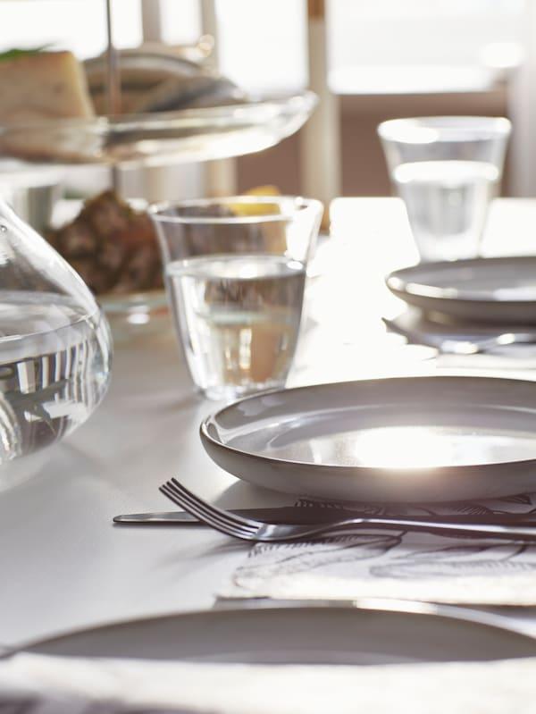 O farfurie de desert gri GLADELIG cu cuțit și furculiță din inox și un pahar transparent pe o masă aranjată.
