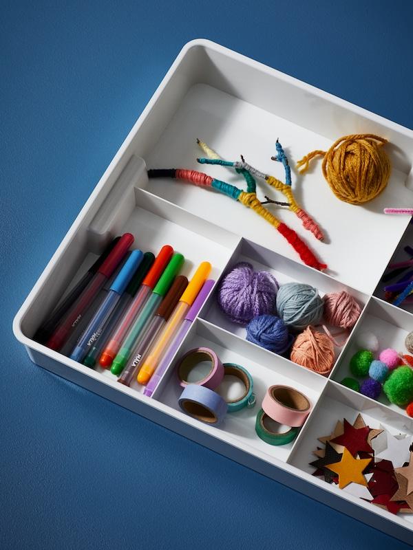 Fehér KUGGIS betét nyolc rekesszel, benne MÅLA vegyes színű filctollak, madzagok és kézműves kiegészítők.