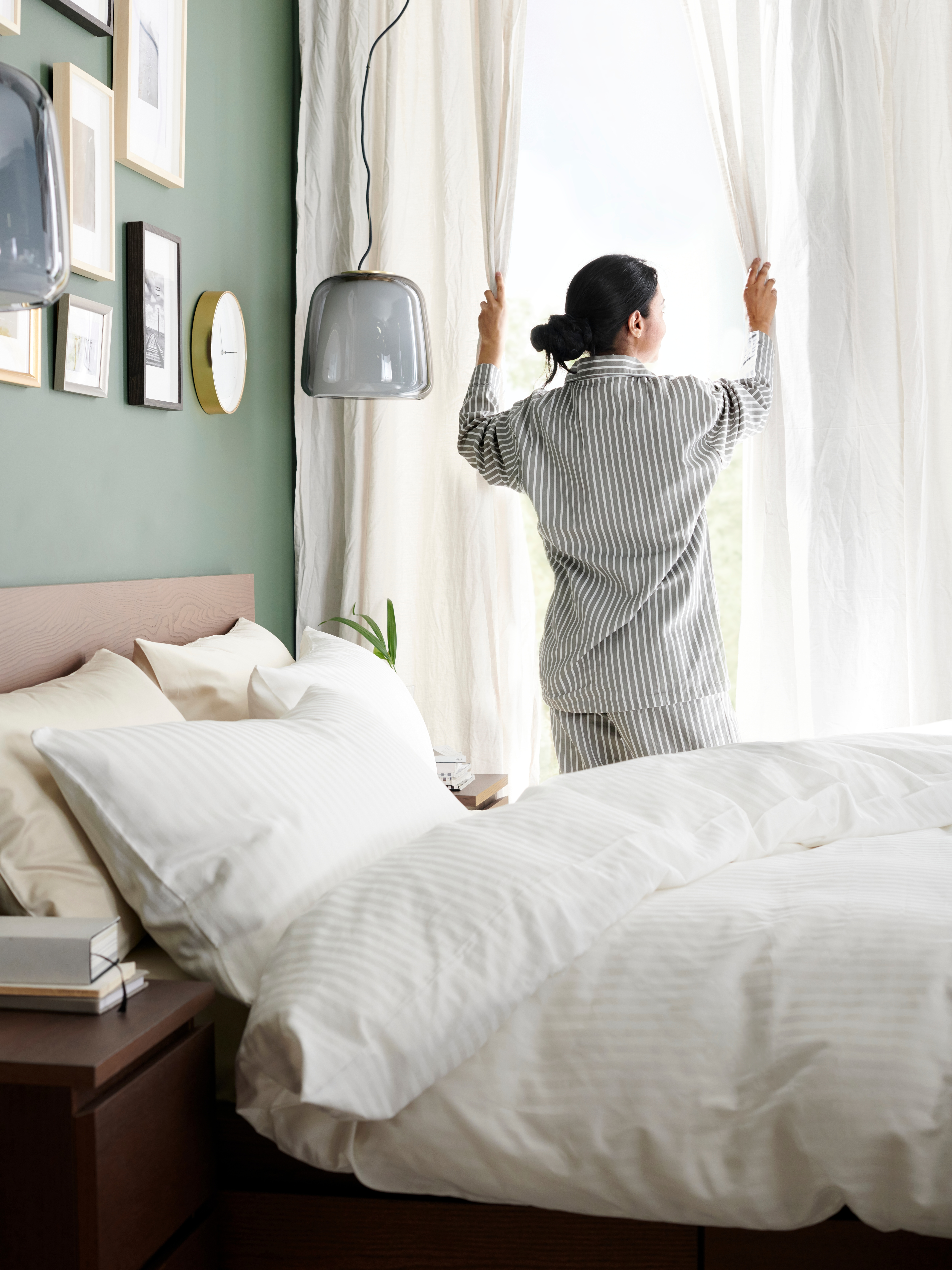 A woman in striped pyjamas opening curtains behind a MALM bed, made up with NATTJASMIN bed linens.