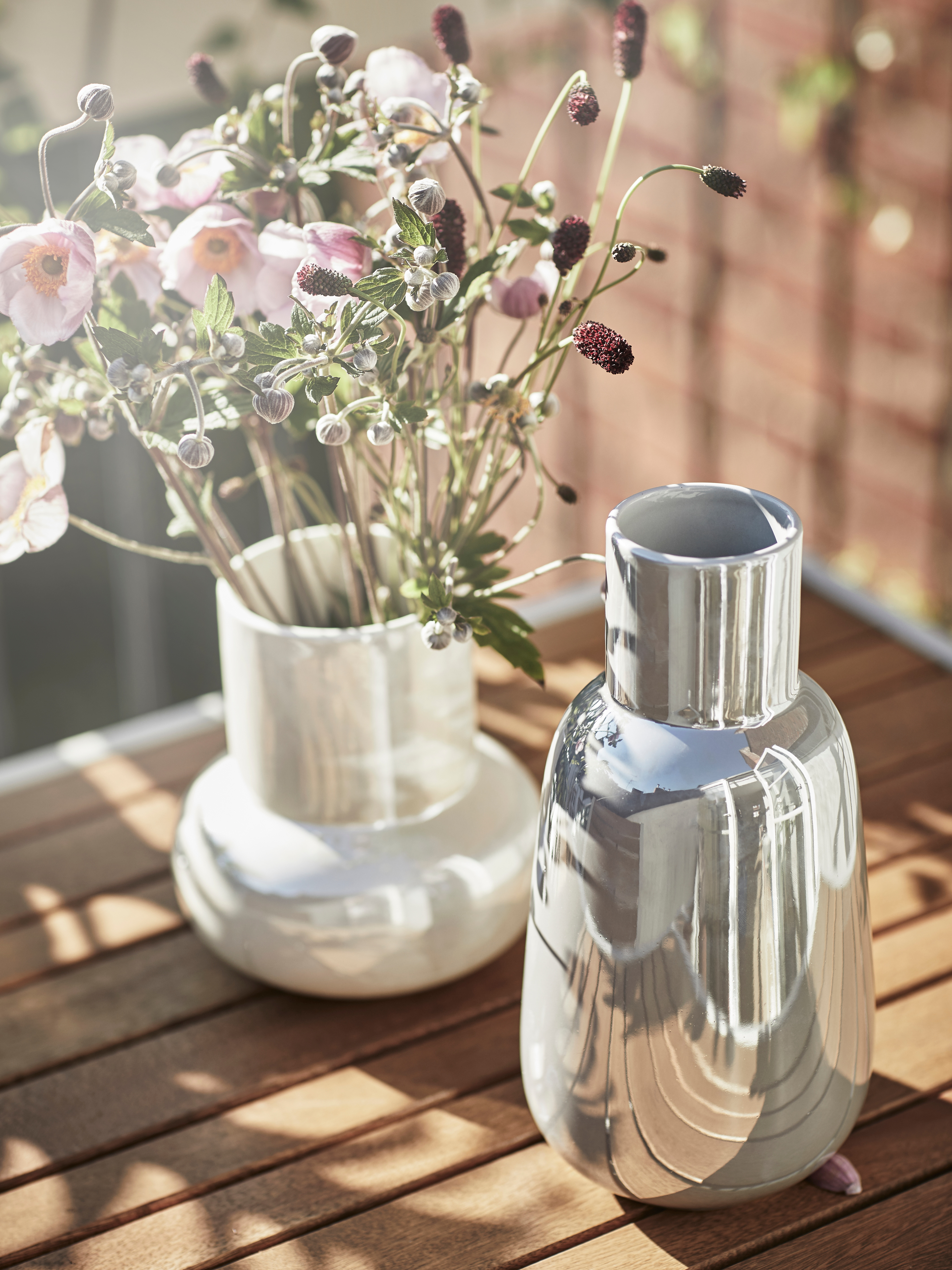 Close-up of a wooden table, displayed a FNITTRIG vase with flowers and an empty silver vase.