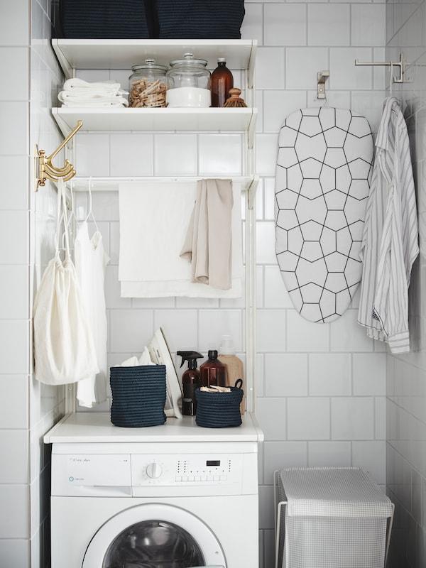 Постирочная комната с настенными плками, стиральной машиной, корзиной для белья, гладильной доской