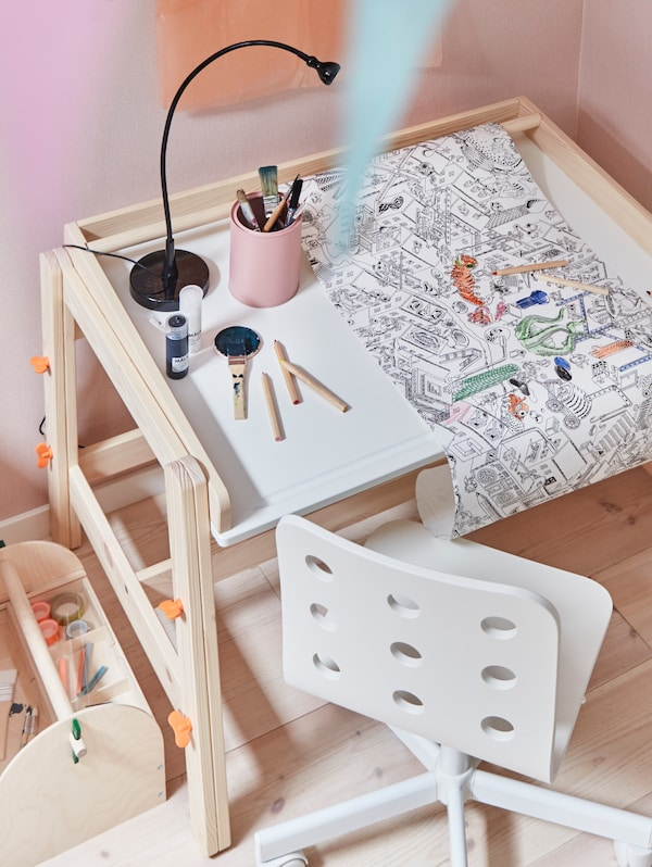 A FLISAT children's desk with a LUSTIGT colouring paper roll on it sits in a corner with a JULES children's desk chair.