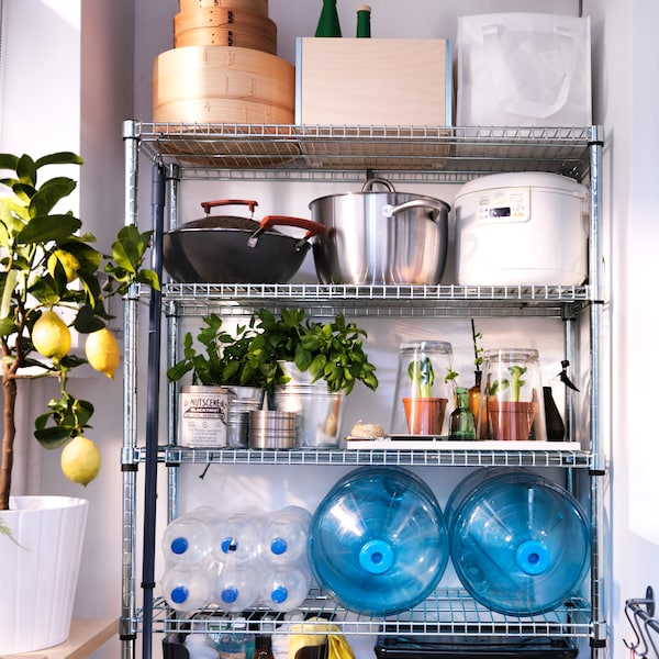 Metal shelves storing kitchen utensils and cookware next to a window with a lemon plant on the windowsill.
