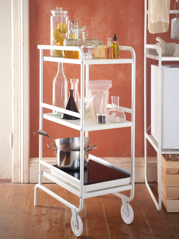 Biely kuchynský vozík SUNNERSTA, na ktorom sú sklené dózy, fľaše a hrnce. Vozík stojí pri dverách, vedľa minikuchyne SUNNERSTA.