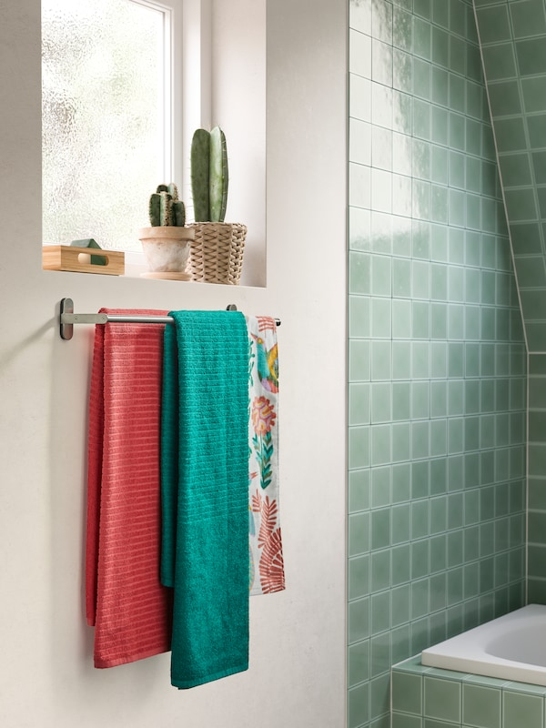 Green and pink towels with woven stripes hang on a BROGRUND towel rail that's wall-mounted under a window.