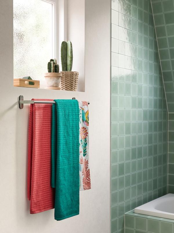 Des serviettes vertes et roses à rayures en relief suspendues à une barre porte-serviettes BROGRUND sous une fenêtre.