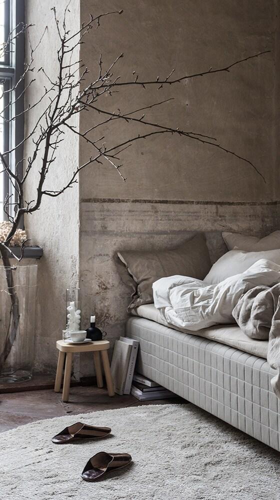 En rustik miljö med en stor dekorativ naken gren i ena sidan, ett par tofflor på mattan ÅDUM bredvid resårbotten SKÅRER med bäddmadrassen TUDDAL på.