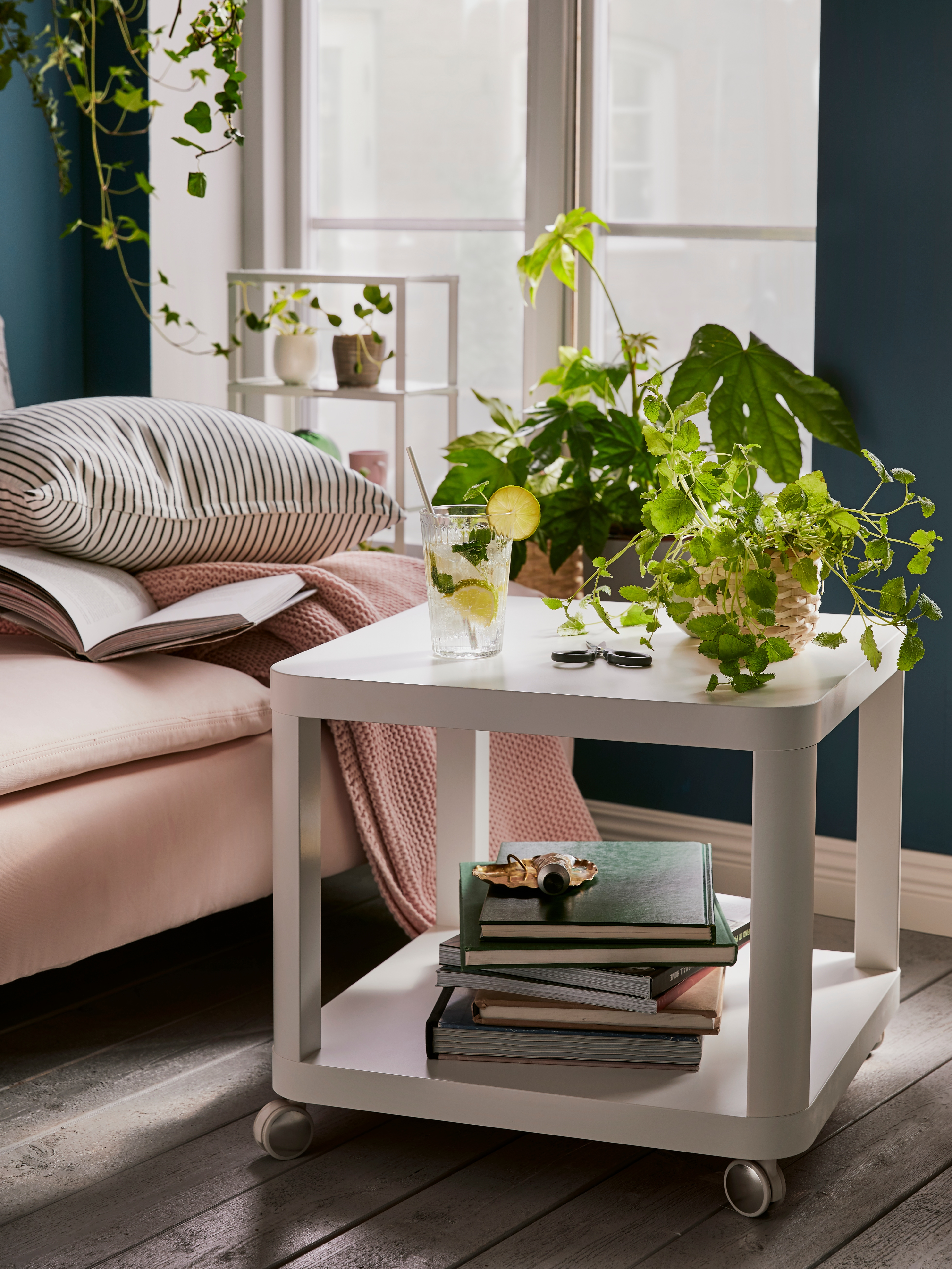 White TINGBY side table with castors in front of a pale pink SÖDERHAMN chaise longue. The table holds books and plants.