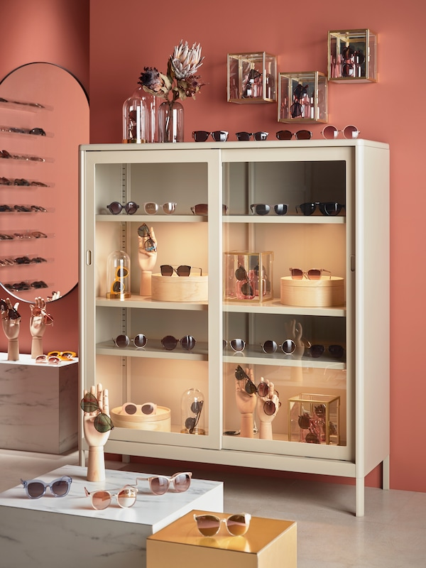 A glass storage cabinet, with lots of sunglasses and boxes on display on the shelves, sunglasses and glass vases on top.