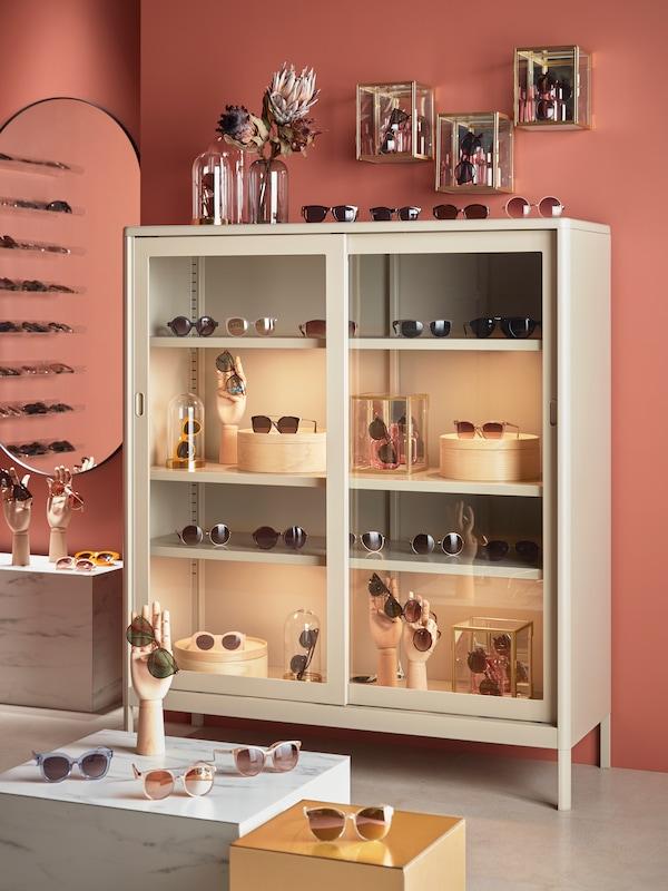Vitrina za shranjevanje z veliko sončnimi očali in škatlami, razstavljenimi na policah, sončna očala in steklene vaze so na vrhu.