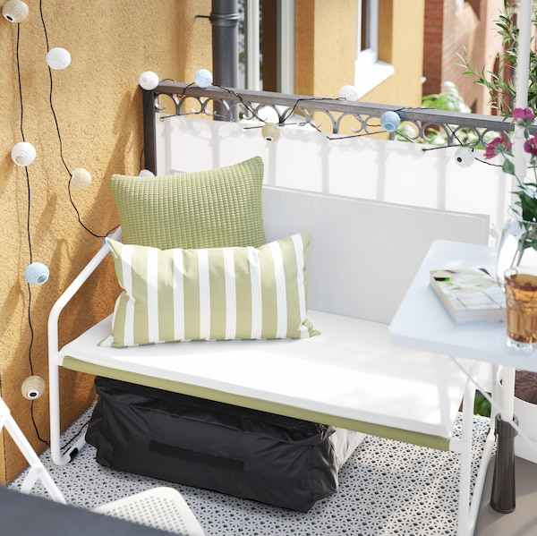 A small two-seat sofa with green decorative cushions and a black storage bag underneath on a balcony.