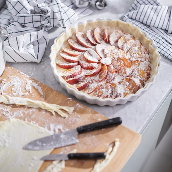 A peach pie in progress dusted with icing sugar, next to a cutting board with pastry trimmings.