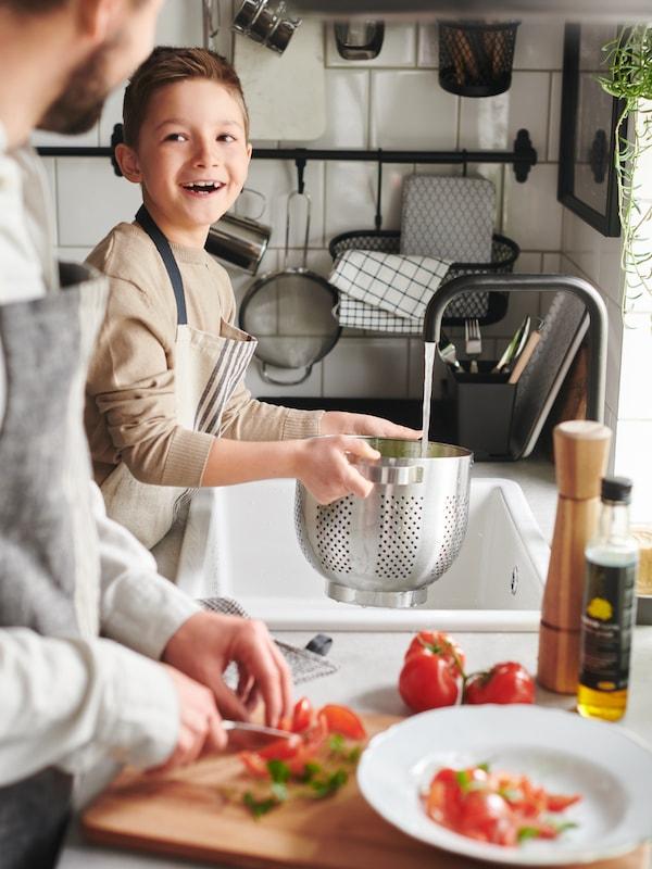 Pai e filho a preparar uma refeição com escorredor de aço inoxidável, tábua de cortar em faia, moinho de especiairias em faia e um prato OFANTLIGT em branco.