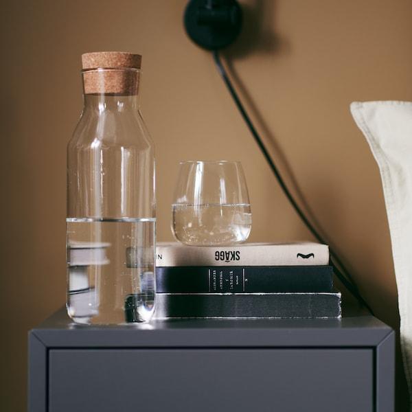 Botella IKEA 365+ con tapón, varios libros y un vaso sobre un armario de color gris oscuro en una habitación.