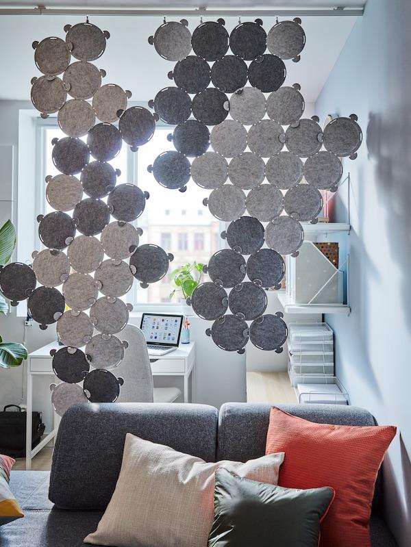 Szare panele dźwiękochłonne służące jako przepierzenie pomiędzy salonem z szarą sofą, a biurem domowym.