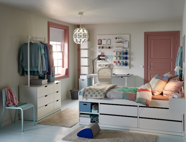 A dorm room featuring a bed with integrated storage along with a desk and hanging clothes storage nearby.