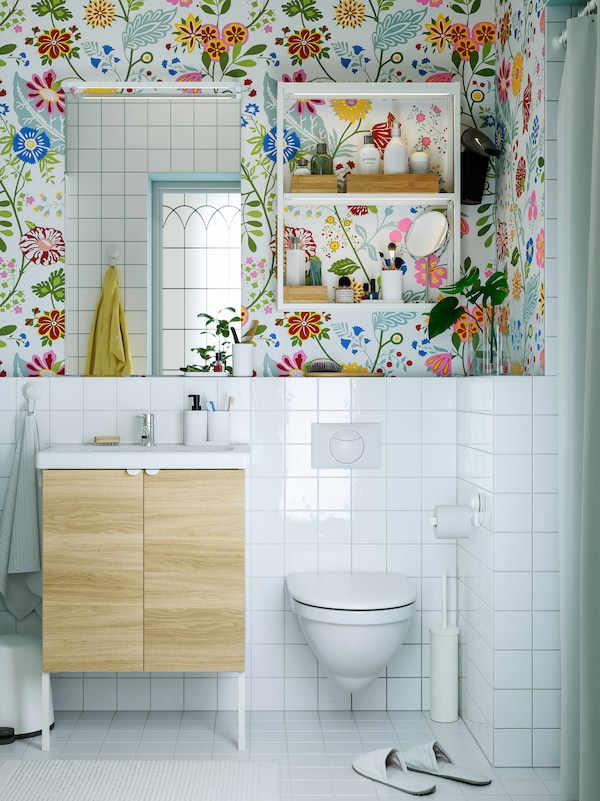 Floral wallpaper, a white wash-basin with wooden doors, a mirror, white open shelves with toiletries above the toilet.