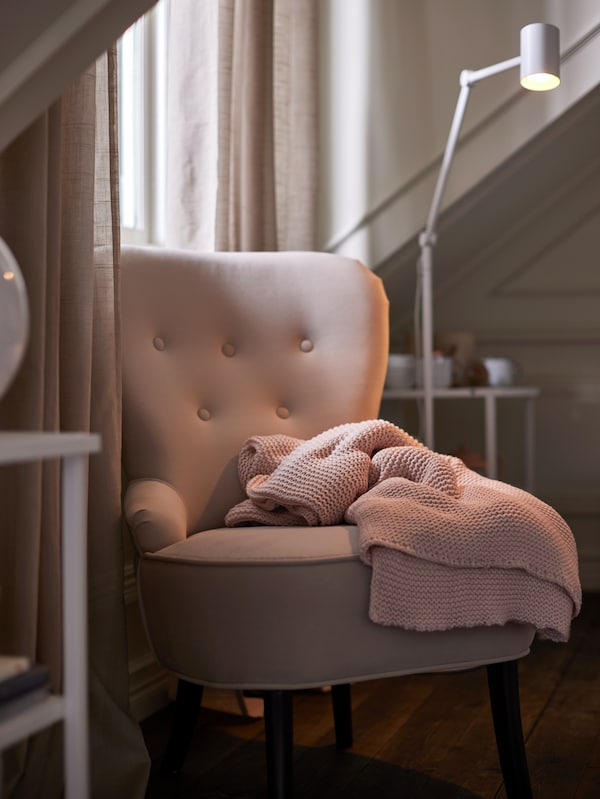 A pale pink knitted throw on a beige REMSTA armchair with a white floor lamp behind, by a window with beige curtains.