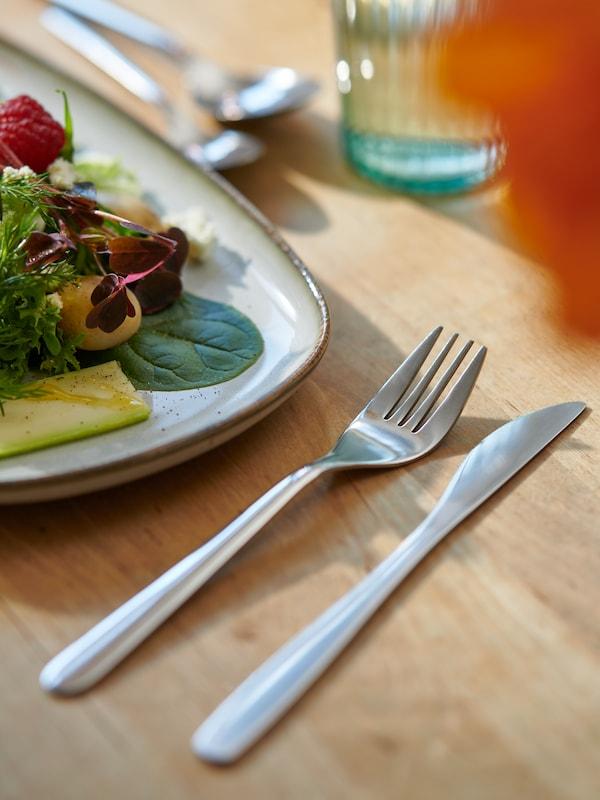 Un solo plato GLADELIG con una ensalada fresca y cubiertos FÖRNUFT a un lado, todo sobre una superficie de madera clara.